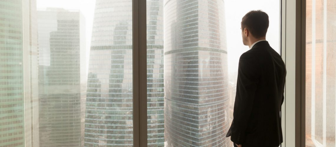 Man in business suit standing with hands in pants pockets looking through window on city landscape with skyscrapers. Businessman thinking about perspectives, dreaming of company success. Back view